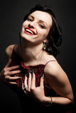 Woman in a red dress. Beautiful young woman in a red dress on a dark background Royalty Free Stock Photography