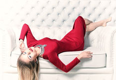 Woman in red dress. Beautiful young woman with stylish make up, elegant jewelry and in red dress posing lying on the white sofa Stock Image