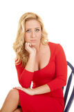 Woman red dress on blue chair hand chin facing Royalty Free Stock Photography
