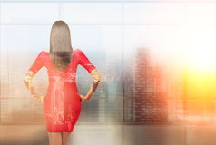 Woman in red dress. Businesswoman in red dress, city view. Back view. Double exposure. Concept of work royalty free stock photography