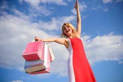 Woman red dress carries bunch shopping bags blue sky background. Feel free buy everything you want. Finally bought. Favorite brands. Tips shop summer sales royalty free stock photo