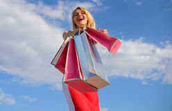 Woman red dress carries bunch shopping bags blue sky background. Finally bought favorite brands. Girl satisfied with. Purchases. Feel free buy everything you stock images