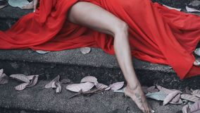 Woman in red dress. Closeup legs of woman in red dress sitting on the concrete stairs - video in slow motion