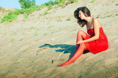 Woman in red dress on coast. Girl dressed in red dress on a coast royalty free stock images