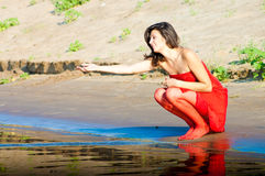 Woman in red dress on coast. Girl dressed in red dress on a coast stock photo