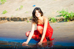 Woman in red dress on coast. Girl dressed in red dress on a coast royalty free stock photos