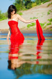 Woman in red dress on coast. Girl dressed in red dress on a coast stock photography