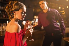 Woman in red dress with cocktail in hand, flirting Royalty Free Stock Images