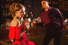 Woman in red dress with cocktail in hand, flirting. Young women in red dress with cocktail in hand, men behind bar counter, flirting. Date in nightclub Royalty Free Stock Photography