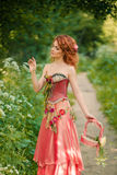 Woman in a red dress collects white flowers. Red-haired woman in a red dress collects white flowers Stock Photography