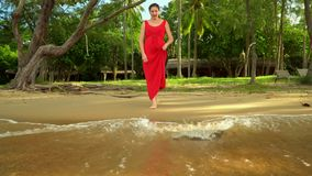 Woman in a red dress costs on the ocean coast.  stock footage