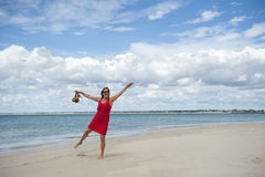 Woman in Red Dress Dancing on the Beach Stock Photography