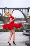 Woman in red dress dancing on the wind. Beautiful blonde woman in the red dress and high heels dancing on the wind at the summer evening Royalty Free Stock Photos