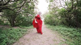 Woman in a red dress is dancing. Woman in a red dress is dancing in the garden stock footage