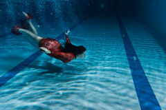 Woman in red dress dives. Royalty Free Stock Photos