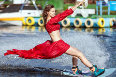 Woman in a red dress does not wakeboard. Her dress is blown by the wind Royalty Free Stock Photography
