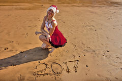 Woman in red dress with drawing on the sand digits 2017. Woman in red dress and Christmas hat on the beach with drawing on the sand digits 2017 Royalty Free Stock Photo