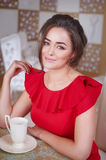 Woman in a red dress drinking tea in the kitchen Royalty Free Stock Photography
