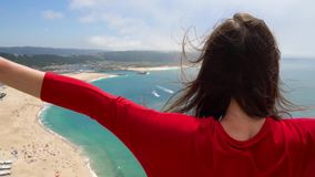 Woman in red dress enjoys a view of the ocean coast near Nazare, Portugal. Slow motion stock footage