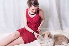Woman in red dress feeding dog on blanket.  Stock Photography