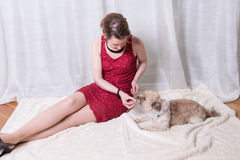 Woman in red dress feeding dog on blanket.  Royalty Free Stock Photos