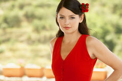 Woman In Red Dress With Flower In Hair. Portrait of beautiful young woman in red dress with flower in hair Stock Photos