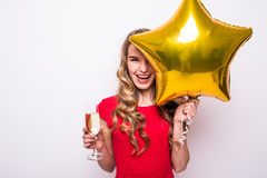 Woman in red dress with gold star shaped balloon smiling and drinking champagne. Pretty young woman in red dress with gold star shaped balloon smiling and Royalty Free Stock Photo
