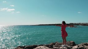 Woman in red dress with hands apart against sun standing on rocky cliff pier enjoying wind and sun. Ocean waves hitting rocky beac. H splashing and creating stock video footage
