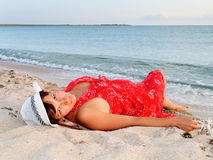 Woman in a red dress and hat on the beach. Portrait of a beautiful young woman in a red dress and hat on the beach Royalty Free Stock Images