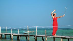 The woman in a red dress and a hat is photographed on Selfie stick. The woman walks on a pier with Selfie stick. Slow. On this video you can see as the woman in stock video