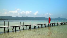 The woman in a red dress and a hat walks on a long wooden pier.phu quoc Island. Slow mothion. White tropical sand. On this video you can see as the woman in a stock video footage