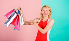 Woman red dress hold bunch shopping bags blue pink background. Buy everything you want. Girl satisfied with shopping. Tips to shop sales successfully. Girl stock photography