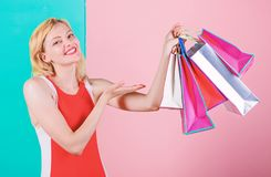 Woman red dress hold bunch shopping bags blue pink background. Girl enjoy shopping or just got birthday gifts. Buy stock photos