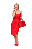 Woman in red dress holding big bag  talking on the cell phone Royalty Free Stock Photo