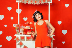 Woman in red dress holding a cake and dreams. Stock Photos