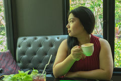 Woman in red dress holding hot coffee cup stock photo
