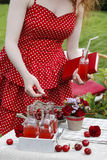 Woman in red dress holding a ripe cherry, bottle of cherry juice Stock Images