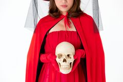 Woman in red dress holding skull on white background. Concept for costume in halloween festival stock image