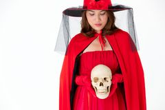 Woman in red dress holding skull on white background. Concept for costume in halloween festival royalty free stock photo