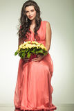 Woman in red dress holding yellow flowers basket and sits Stock Photography
