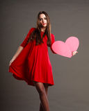 Woman in red dress holds heart sign Stock Photo