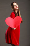 Woman in red dress holds heart sign Royalty Free Stock Image
