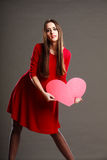 Woman in red dress holds heart sign Stock Images