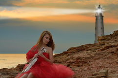 Woman in red dress holds violin at sea shore Royalty Free Stock Images