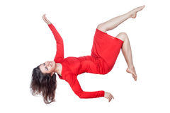 Woman in red dress laughs and falls. Floating woman in a red dress on a white background Stock Image