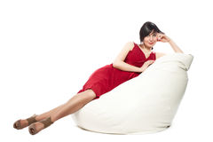 Woman in red dress laying on armchair. Woman in red dress laying on the armchair. Relaxing and smiling Royalty Free Stock Image