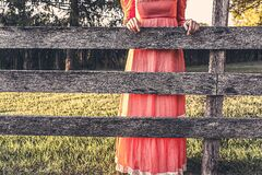 Woman in red dress leaning on fence Stock Images