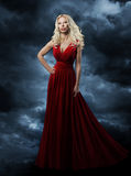 Woman in red dress, long hair blonde in fashion evening gown over sky background, hand on hip royalty free stock image