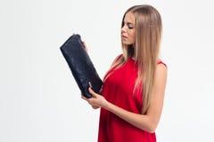 Woman in red dress looking at handbag Stock Photo