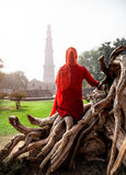 Woman in red dress looking at Qutub Minar Royalty Free Stock Photos